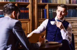 Aristocrats spend leisure in intelligent company. Tea party concept. Oldfashioned intelligent men drink tea according to british tradition. Men in suit sit in library or retro interior, defocused.