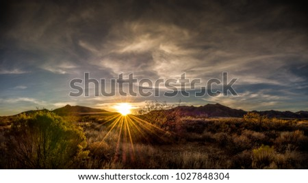 Arizona desert mountain sunset with the sun exploding over the mountains as it sets