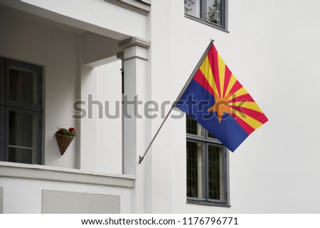 Arizona flag. Arizona state flag hanging on a pole in front of the house. State flag waving on a home displaying on a pole on a front door of a building. Flag raised at a full staff.