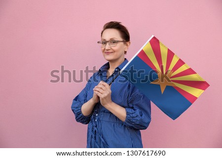 Arizona flag. Woman holding Arizona state flag. Nice portrait of middle aged lady 40 50 years old holding a large state flag over pink wall background on the street outdoor.
