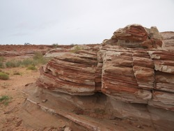 Arizona red desert landscape scenic view near Lake Powell, red rock strata, layered red rock formation, car in background