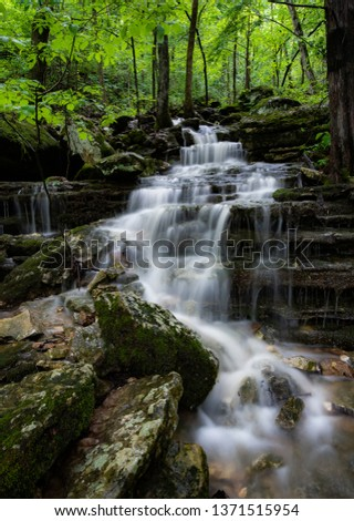 Arkansas cascade deep in the lush Ozark mountains. Lush green Spring foliage, soft water and the rocky ridge gives a textured contrast to the forest scene deep in the dense wilderness.