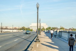 Arlington Bridge Leads to Lincoln Memorial in Washington DC, USA. Vehicles Crossing the Bridge and People Walking and Hiking on the Pavement on a Sunny Day.