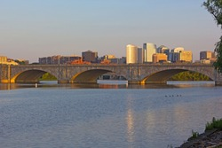 Arlington Memorial Bridge and Rosslyn suburb at sunset, Washington DC, USA. Panoramic view on Potomac River and Washington DC metro area buildings across the river.