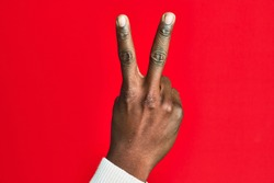 Arm and hand of african american black young man over red isolated background counting number 2 showing two fingers, gesturing victory and winner symbol