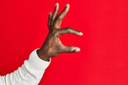 Arm and hand of african american black young man over red isolated background picking and taking invisible thing, holding object with fingers showing space