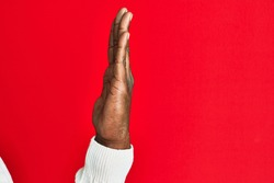 Arm and hand of african american black young man over red isolated background showing side of stretched hand, pushing and doing stop gesture