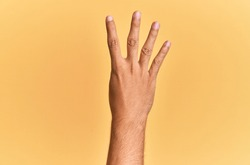 Arm and hand of caucasian man over yellow isolated background counting number 4 showing four fingers