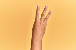Arm and hand of caucasian man over yellow isolated background counting number 3 showing three fingers