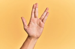 Arm and hand of caucasian man over yellow isolated background greeting doing vulcan salute, showing hand palm and fingers, freak culture