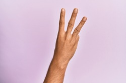 Arm and hand of caucasian young man over pink isolated background counting number 3 showing three fingers