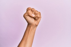 Arm and hand of caucasian young man over pink isolated background doing protest and revolution gesture, fist expressing force and power