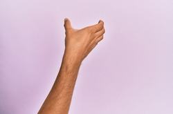 Arm and hand of caucasian young man over pink isolated background holding invisible object, empty hand doing clipping and grabbing gesture