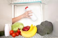 Arm inside refrigerator full of fruit and vegetables.