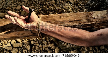 Arm of Christ nailed to a wooden cross in a concept of his martyrdom, suffering, crucifixion and resurrection today celebrated over the Easter holiday in banner format #715659049