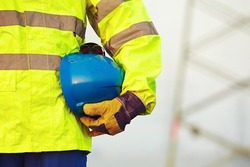 Arm of worker is holding protective helmet