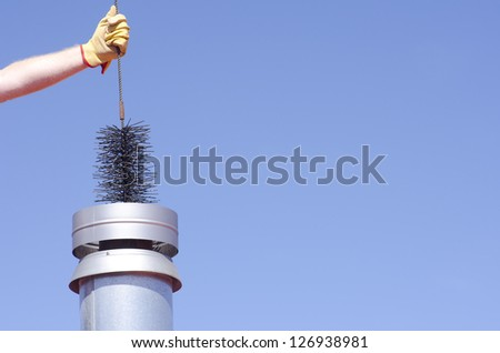 Arm with yellow glove holding sweeper to clean chimney on house, isolated with blue sky as background and copy space.
