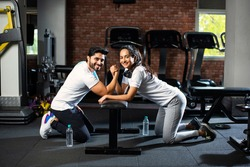Arm wrestling challenge between a young Indian asian couple - having fun in the gym