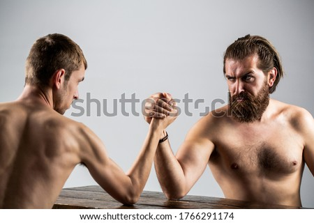 Arm wrestling. Heavily muscled bearded man arm wrestling a puny weak man. Arms wrestling thin hand, big strong arm in studio. Two man's hands clasped arm wrestling, strong and weak, unequal match.