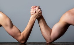 Arm wrestling. Heavily muscled man arm wrestling a puny weak man. Arms wrestling thin hand and a big strong arm in studio. Two man's hands clasped arm wrestling, strong and weak, unequal match.