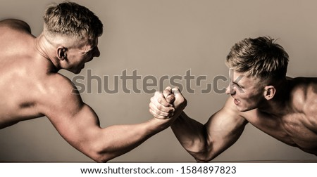 Arm wrestling. Two men arm wrestling. Men measuring forces, arms. Hand wrestling, compete. Rivalry, closeup of male arm wrestling. Hands or arms of man. Muscular hand.