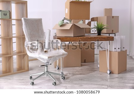 Armchair and carton boxes with stuff in room. Office move concept