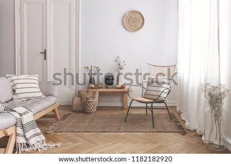Armchair on rug next to bench with plants in white loft interior with wooden sofa. Real photo