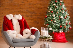 Armchair with Santa Claus costume in room decorated for Christmas