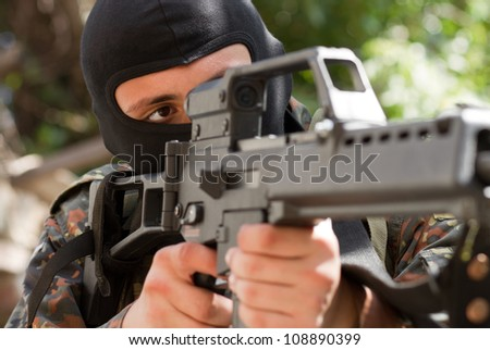 Armed and dangerous man in black mask targeting on optical scope