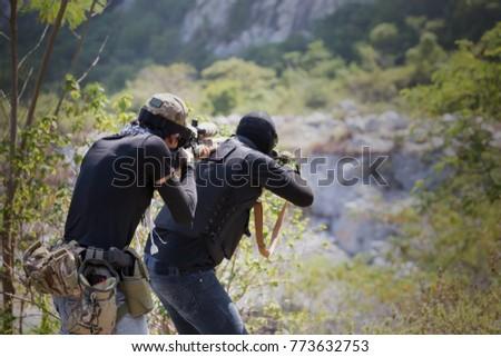 Shutterstock Armed guerrillas walking in the forest.