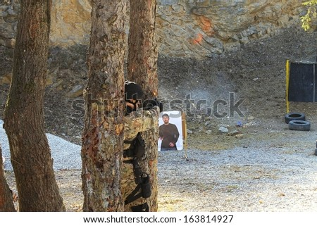 Armed man behind the tree shoots at a target