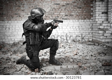 Armed man in protective cask with a pistol on the ruined building background.