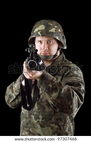 Armed man pointing a rifle in studio