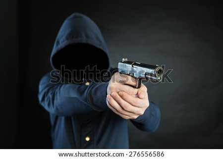 Armed person in a hoodie is pointing a handgun at the target.