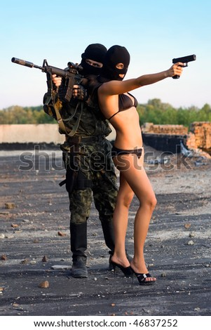Armed soldier and sexy woman in black masks