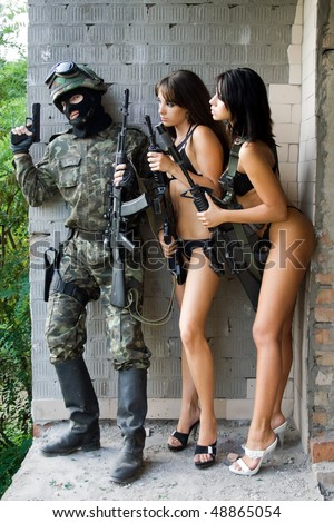 Armed soldier and two sexy women waiting in ambush