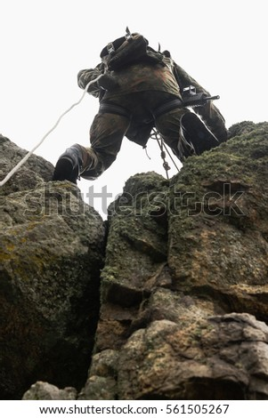 Shutterstock Armed soldier climb on rock with rope.Mountaineering military man with full combat ammunition climbing on mountain in camouflage clothing.Guerrilla soldiers.Ukrainian national guard patrol border