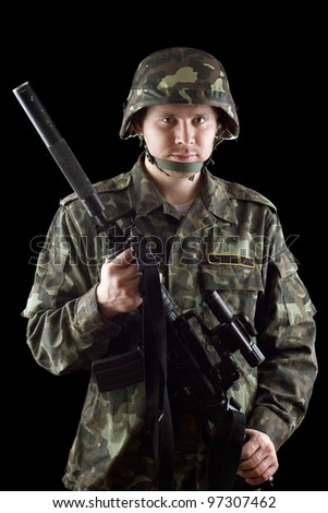 Armed soldier grasping m16 in studio. Isolated