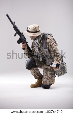 Armed Soldier in camouflage with explosive in his hand - shot in white studio