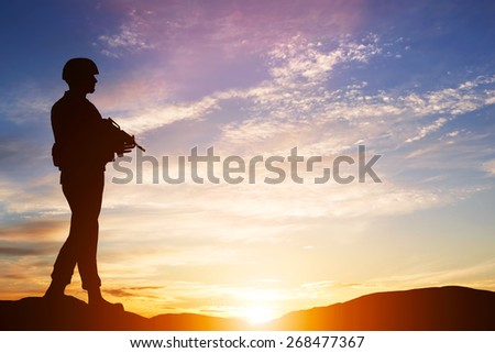 Armed soldier with rifle standing and looking on horizon. Silhouette at sunset. War, army, military, guard.