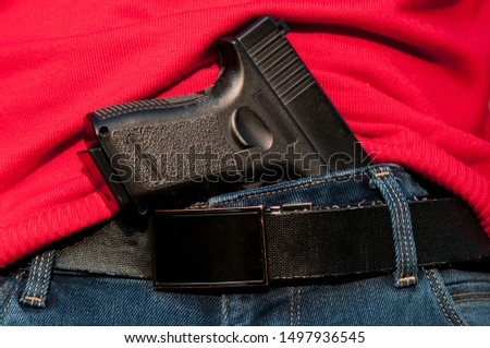 armed with a gun. hides the gun by the belt. use of firearms