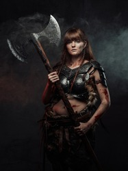 Armed with two handed axe nordic grimy amazon in dark armour with brown hairs poses in dark background with smoke.