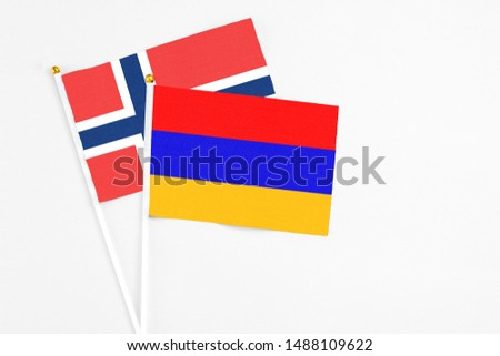 Armenia and Norway stick flags on white background. High quality fabric, miniature national flag. Peaceful global concept.White floor for copy space. #1488109622