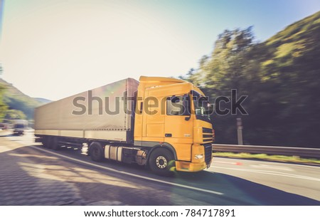 Armenis, Romania - 10/02/2017 - Yellow moving DAF truck coupled with semi-trailer in motion located on the road #784717891