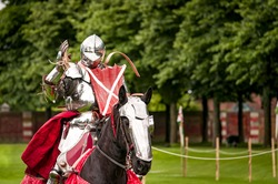 Armored knight suited for battle on horseback, charging in gallop. Galloping it the fastest gait of a horse, and because of the speed the warrior looks even more impressive