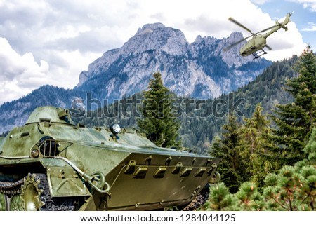 Armored troop-carrier on background of Alps mountains. Military helicopter in the sky.