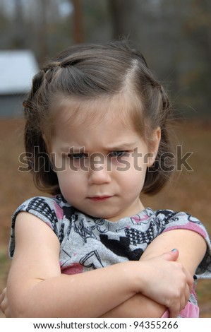 Arms crossed and eyebrows puckered, this little girl is upset and pouting.  She is standing outside and image is closeup.
