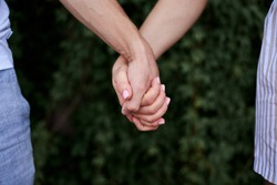 Arms of young couple in love, embracing. Close-up picture of romantic couple hands holding together in front of green leaves wall in summer. Romantic relationship. Valentines day