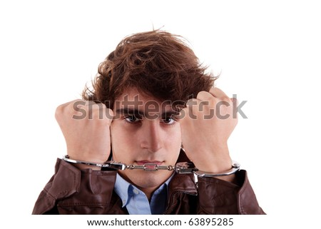 Arms on the face, of a young man, with a handcuffs on the hands, isolated on white background - stock photo