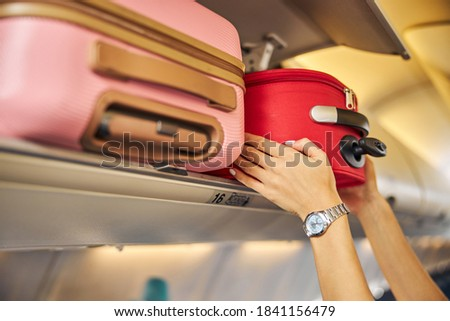 Arms shoving a small piece of luggage to the top shelf of an aircraft Foto stock ©